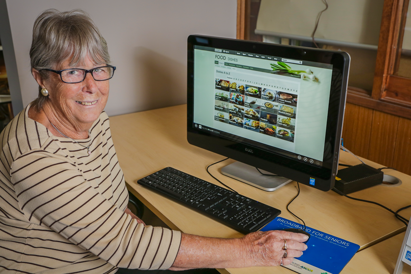 Smiling lady searching for recipes on the internet.